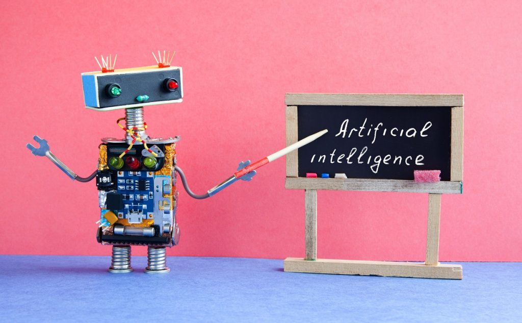 Artificial intelligence concept. Robot teacher explains modern theory. Classroom interior with handwritten quote on black chalkboard. Pink blue colorful background